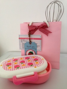 Strawberry cake mix, mini whisk and lunch box as party favour for the children